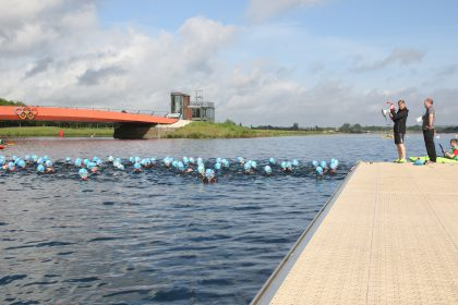 Group of people swimming with swim caps on in Dorney Lake in Eton, with marshalls watching over them.