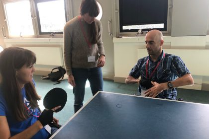 Three people practicing table tennis at the Regain Information Day
