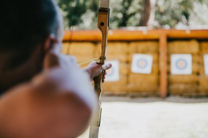 Man with a bow and arrow taking aim at targets