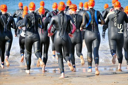 group of open water swimmers in swim hats and wetsuits run into a lake