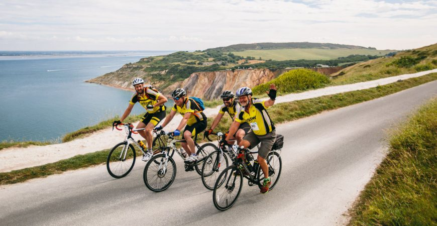 Team of four men cycling along the Isle of Wight coastline and smiling
