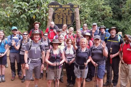 Group of Dream Challenges participants standing at the gate of the Mount Kilimanjaro National Park in Tanzania